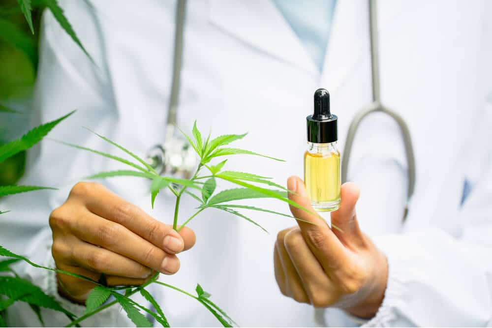 Person in lab coat holding CBD oil dropper
