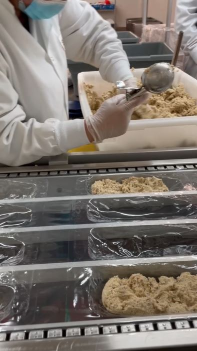 Scooping human-grade Smalls cat food into containers